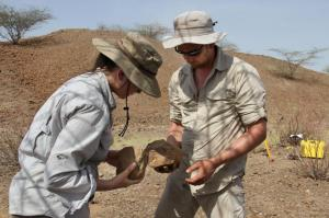 """In this undated photo made available in May 2015 by the Mission Prehistorique au Kenya - West Turkana Archaeological Project, Sonia Harmand and Jason Lewis hold stone tools found in the West Turkana area of Kenya. The artifacts, dated at 3.3 million years old, are much older than the earliest known trace of our own branch of the evolutionary family tree. So it's a new challenge to the traditional idea that only members of our branch made stone tools. The discovery was reported in the journal Nature on Wednesday, May 20, 2015. (MPK-WTAP via AP)"""